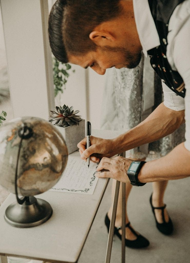 Officiant signing the marriage certificate on a table with a succulent and golden globe at Prospect House in Dripping Springs, Texas. Photograph by Austin, Texas wedding photographer Nikk Nguyen.