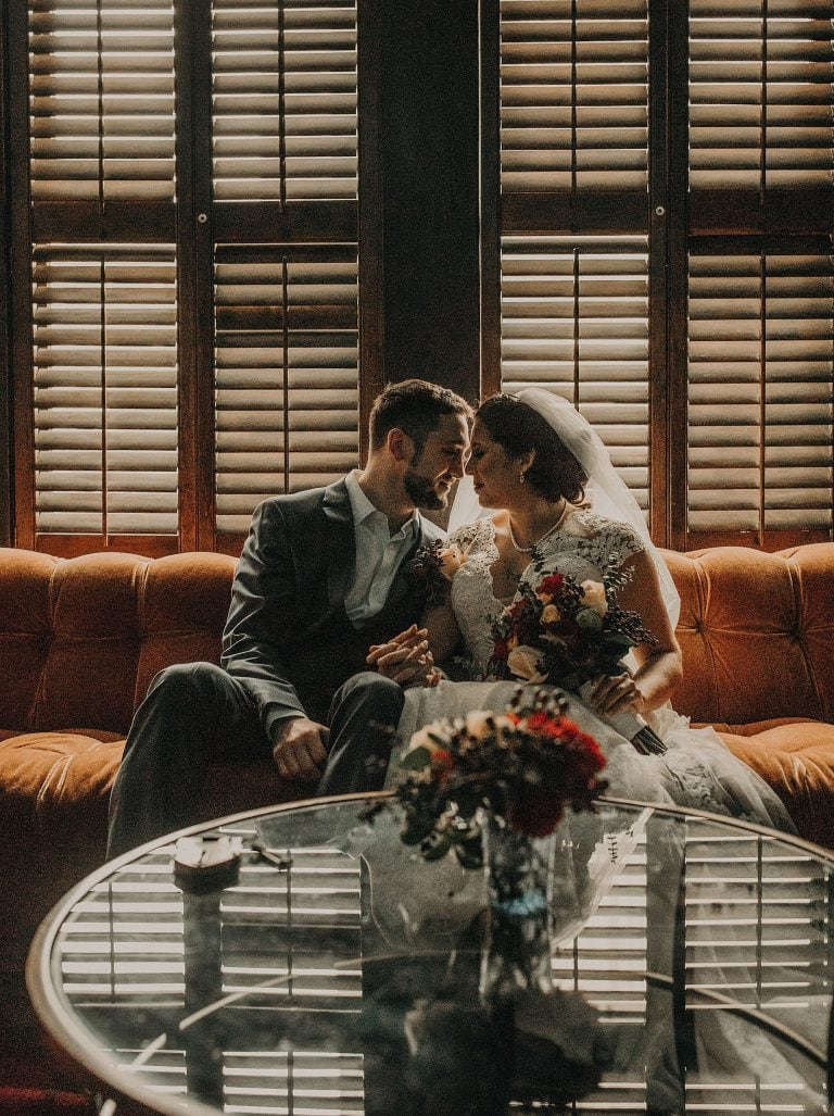 Bride and groom sit on a couch with their foreheads touching in a dimly lit room of the Havana Hotel in San Antonio, Texas. Photograph by Austin, Texas wedding photographer Nikk Nguyen.