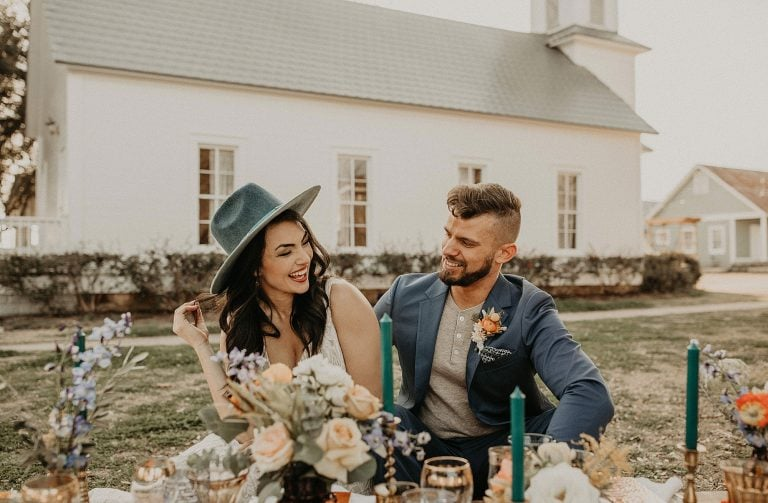 bohemian style bride and groom sitting on cushions at a wooden table in front of a church at Star Hill Ranch in Austin, Texas