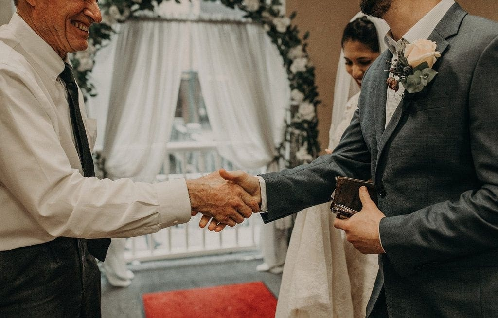 Groom, while his wallet and with the bride standing behind him on his right, shakes the officiants hand. Photograph by Austin, Texas wedding photographer Nikk Nguyen.