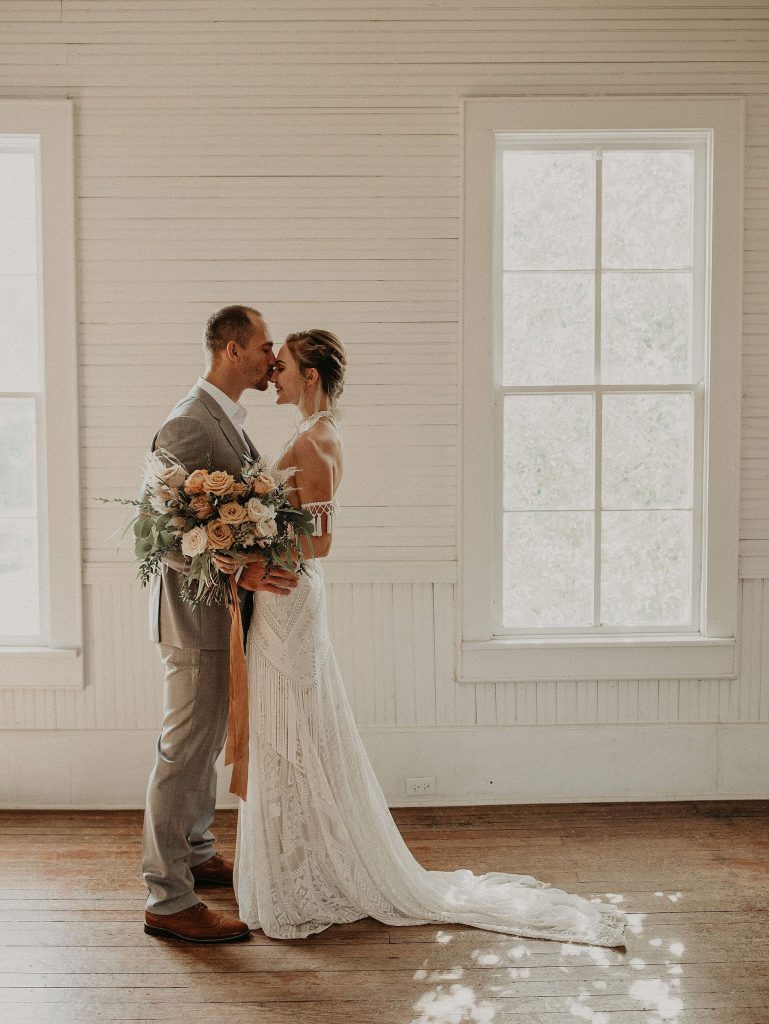 Bride holding her bouquet as the groom embraces her and kisses her forehead in a white wooden room with natural wooden floors at Star Hill Ranch in Bee Cave, Texas. Photograph by Austin, Texas wedding photographer Nikk Nguyen.