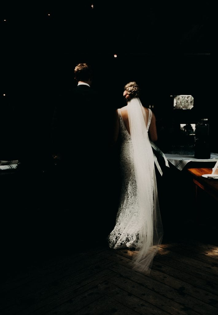 Shot from behind as the bride and groom stand side-by-side in a dark room. Photograph by Austin, Texas wedding photographer Nikk Nguyen.