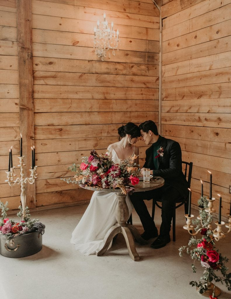 Bride and groom facing each other with their foreheads touching while sitting at a table decorated and surrounded by bohemian style florals and arrangements in a room with wooden panel walls at The Addison Grove in Austin, Texas. Photograph by Austin, Texas wedding photographer Nikk Nguyen.