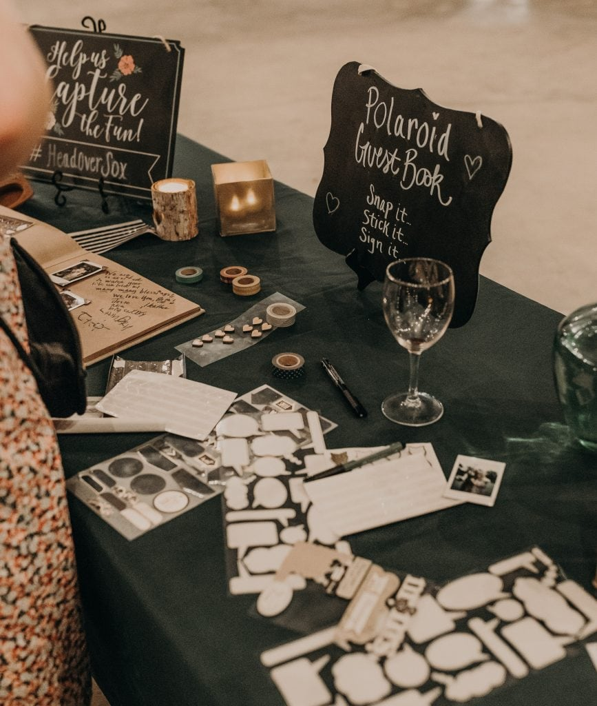 "Wedding guest book table decorated with candles and containing various stickers and two black chalkboard signs that say ""Help Us Capture the Fun! #HeadOverSox"" and ""Polaroid Guest Book. Snap it. Stick it. Sign it."" Photograph by Austin, Texas wedding photographer Nikk Nguyen."