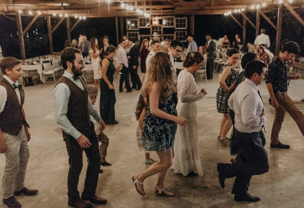 Bride and groom line dancing with wedding guests at The Homestead in Paige, Texas. Photograph by Austin, Texas wedding photographer Nikk Nguyen.