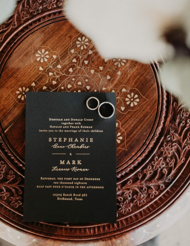 Bird's eye view of a black and gold wedding invitation with bride and groom's wedding rings on a decorated wooden table. Photograph by Austin, Texas wedding photographer Nikk Nguyen.