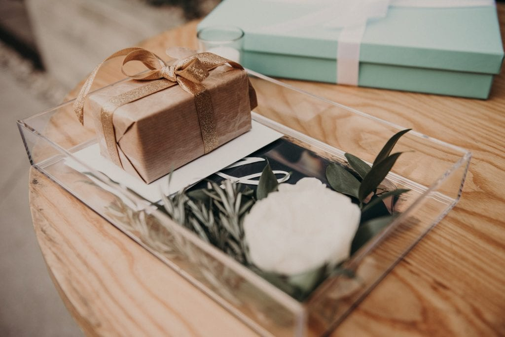 A glass container resting on a wooden table with a small wrapped gift, a flower, and an envelope. Photograph by Austin, Texas wedding photographer Nikk Nguyen.