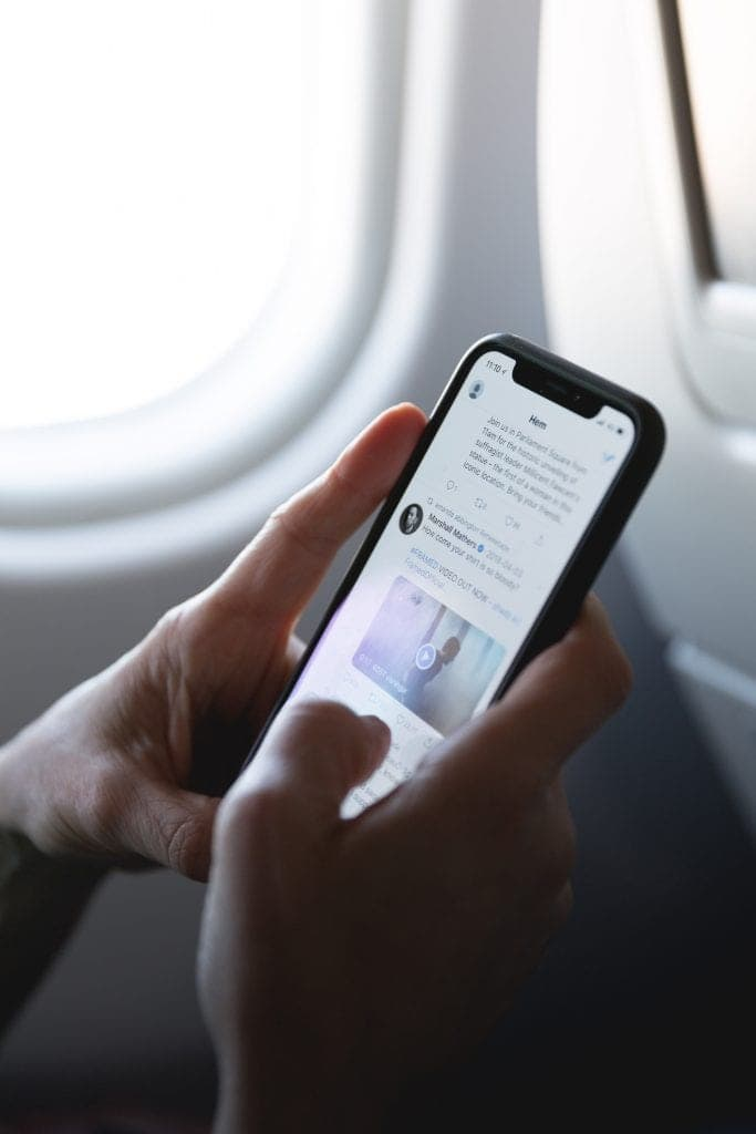 Two hands holding an iPhone and scrolling through a Twitter newsfeed while sitting on an airplane.
