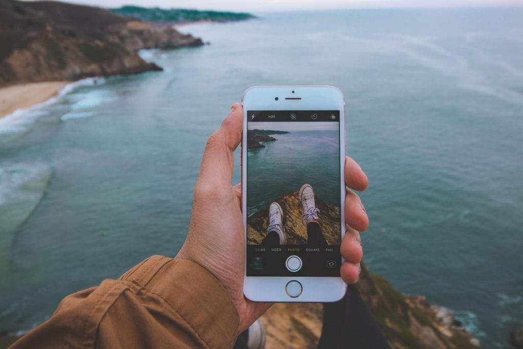 A person's hand holding an iPhone while taking a picture of their feet in Converse shoes as they sit on a rock overlooking the ocean and the oceanside cliffs.