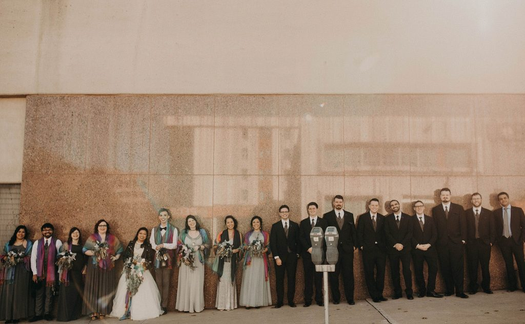 A wedding party lined up against a building in downtown Austin, Texas. Photograph by Austin, Texas wedding photographer Nikk Nguyen.