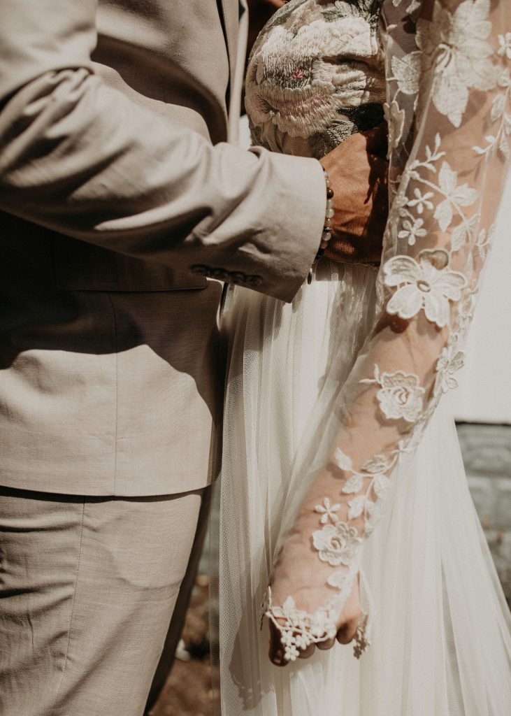 Close up of the waists of the bride and groom with the groom's hand around the bride's waist. Photograph by Austin, Texas wedding photographer Nikk Nguyen.