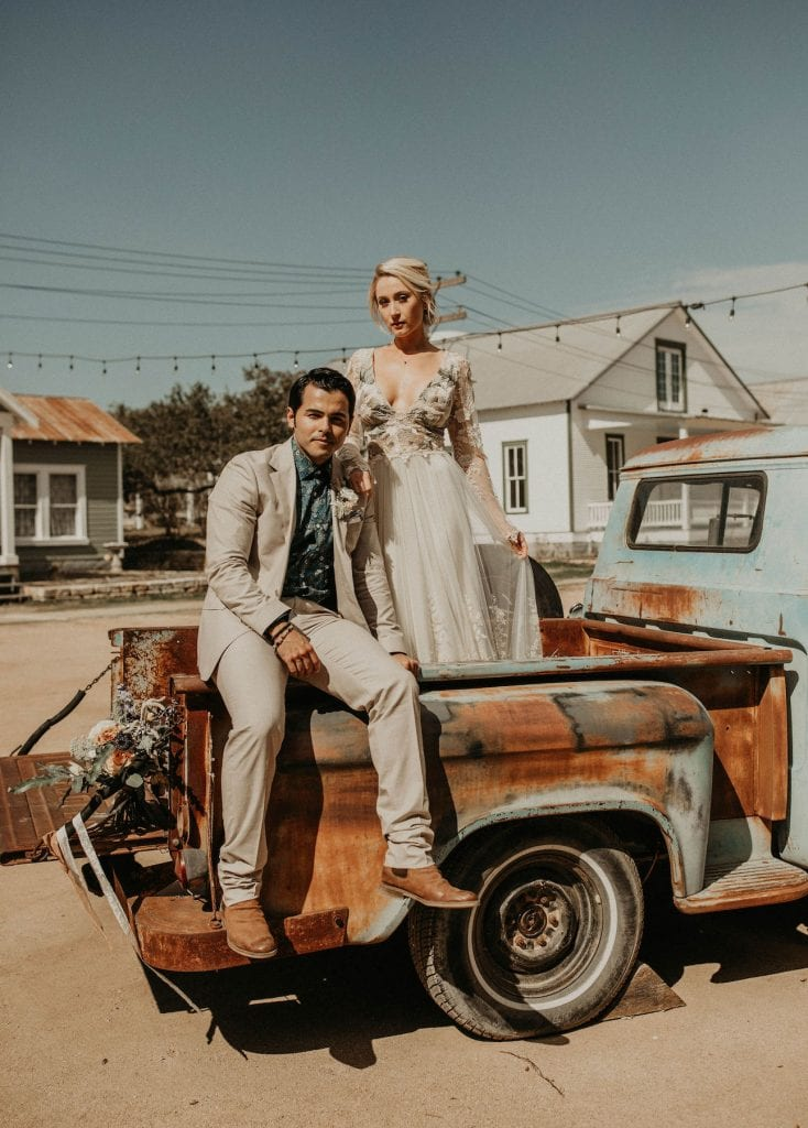 Groom sits on edge of the bed of an old rusty pickup truck while bride stands in the bed of the truck behind him with her arm resting on groom as they look at the camera at Star Hill Ranch in Austin, Texas. Photograph by Austin, Texas wedding photographer Nikk Nguyen.