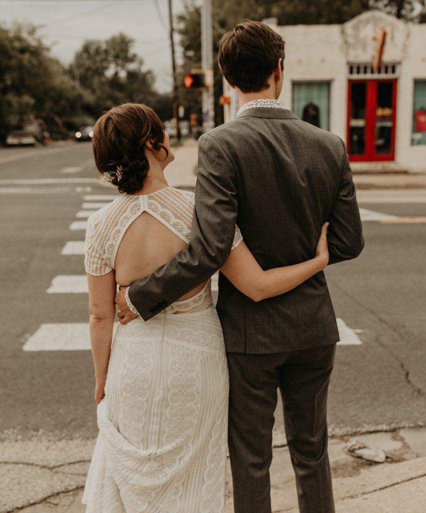 Bride and groom with their arms wrapped around each other as they wait to cross the cross-walk in downtown Austin, Texas. Photograph by Austin, Texas wedding photographer Nikk Nguyen.