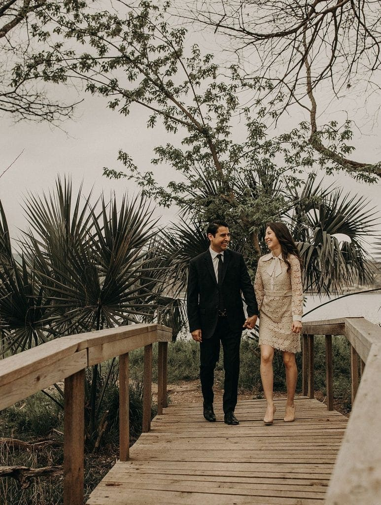 Bride to be and groom to be smiling as they walk hand in hand over a wooden bridge surrounded by palm trees at The Contemporary Austin - Laguna Gloria in Austin, Texas. Photograph by Austin, Texas wedding photographer Nikk Nguyen.