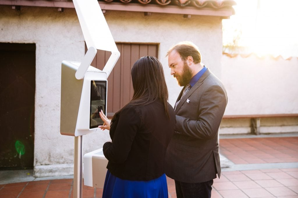A couple adjusting the settings on a photo booth screen in front of a Spanish style building.