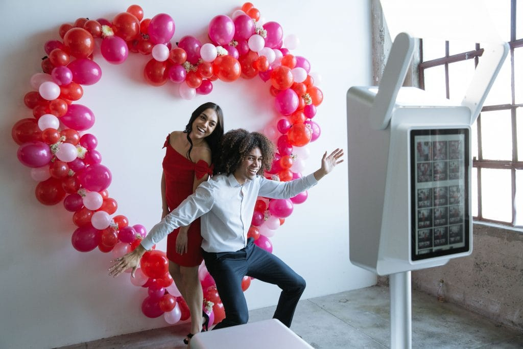 A couple posing for a photo booth in front of red balloons in the shape of a heart.