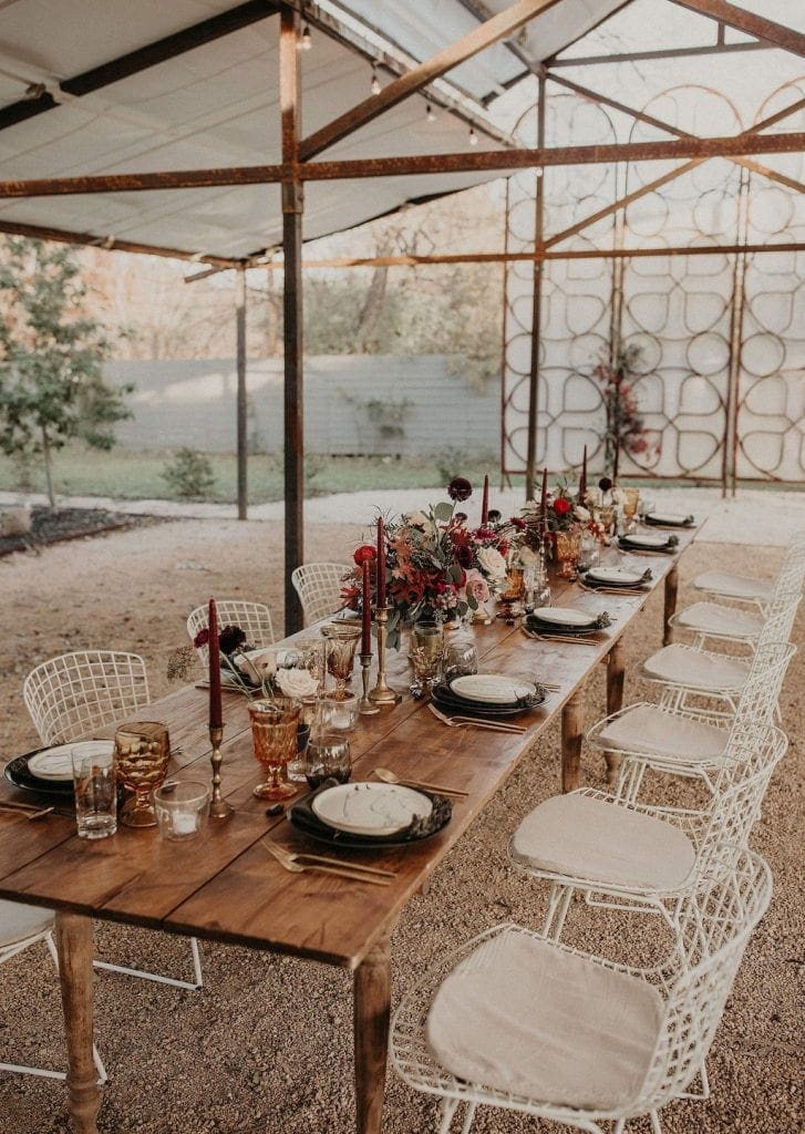 Wooden table sits outside under a canopy and is set with flatware, candles and flowers with white, metal chairs around it.
