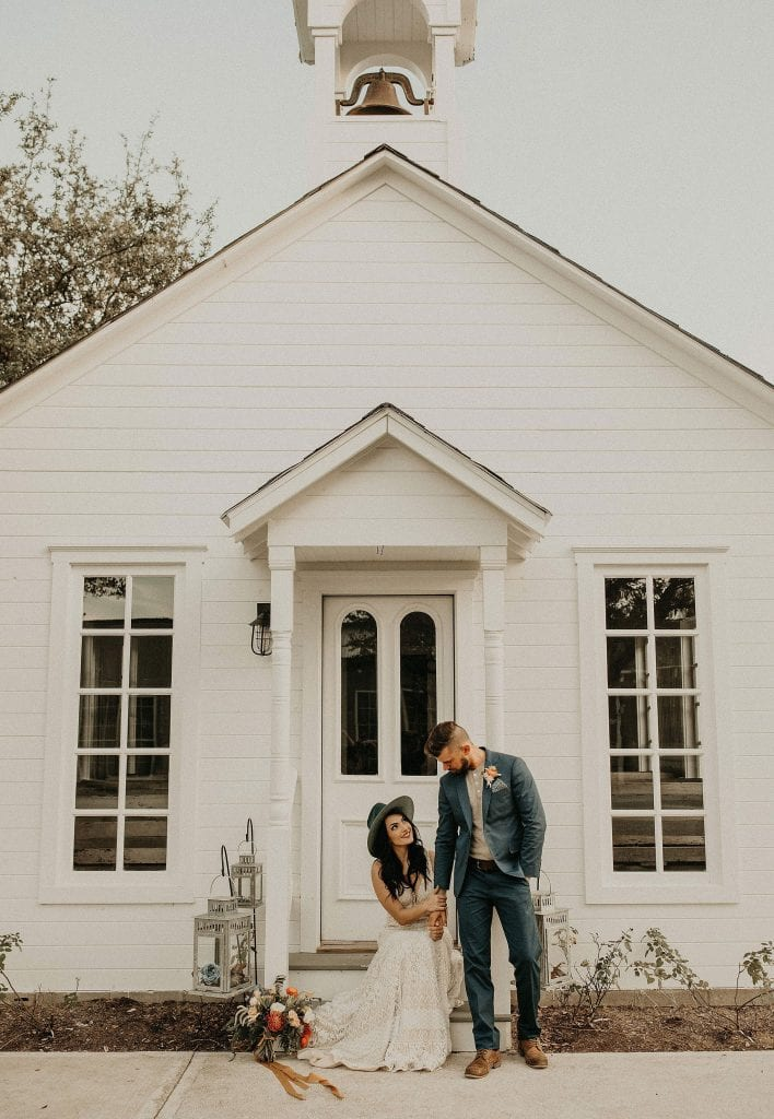 Bride sitting on the steps of a chapel holding the arm of the groom while he looks down at her while standing next to her at Star Hill Ranch in Bee Cave, Texas. Photograph by Austin, Texas wedding photographer Nikk Nguyen.
