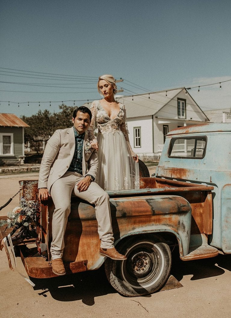 bride standing in the bed of a vintage pickup while resting her arm on the groom who is sitting on the side of the bed of the pickup as they both look toward the camera, at Star Hill Ranch in Austin, Texas
