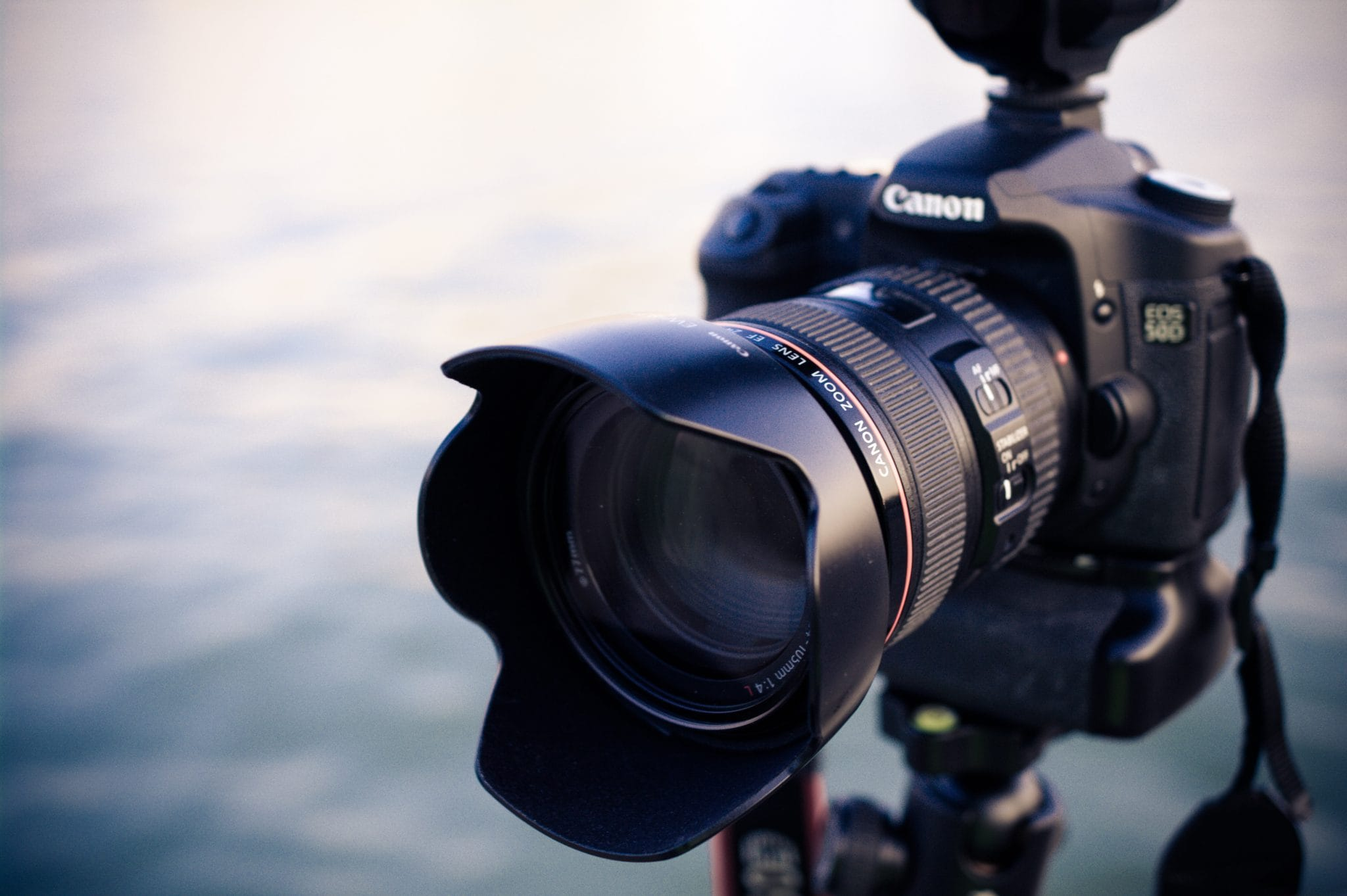 Close up photo of a Canon DSLR camera with extended lens in front of a body of water.