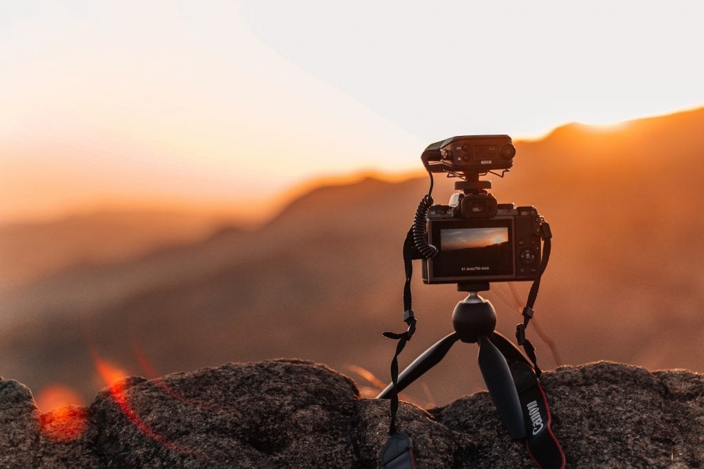 A camera on a small tripod perched on a rock capturing the sun setting over the mountains.