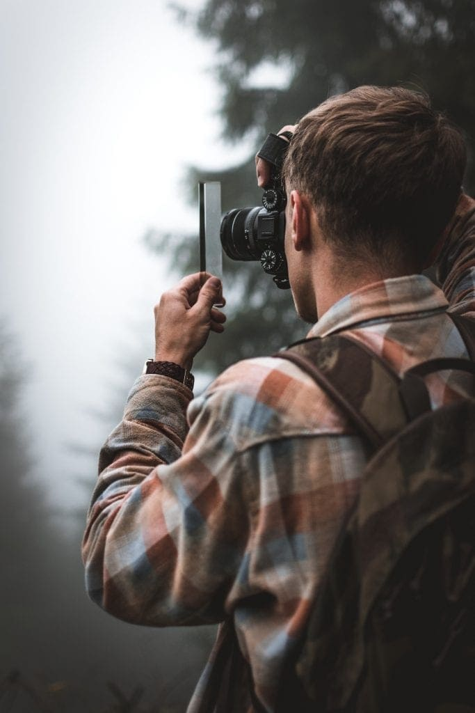 Young man in a plaid shirt and carrying a backpack taking a close-up photo of a piece of glass he is holding with his camera while standing around trees.