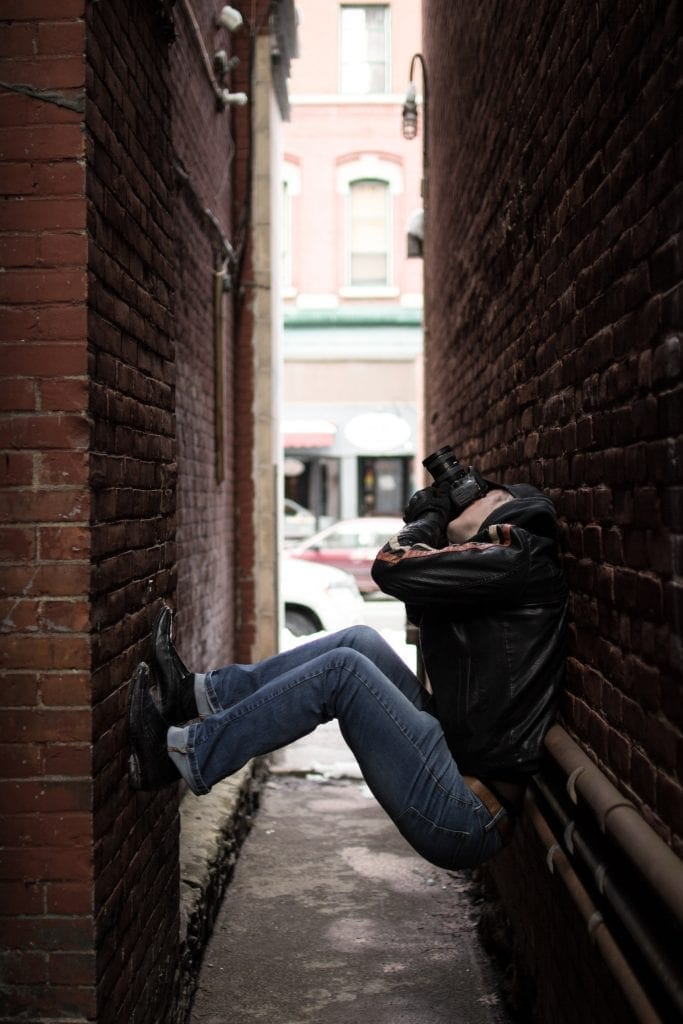 Man with his back against a brick wall and his feet propped up against the opposite brick wall in an alley way taking a photo facing upwards with his camera