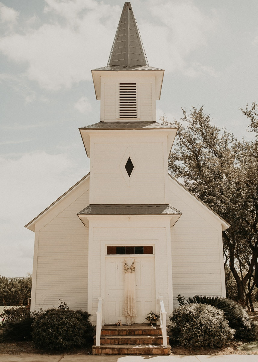 White chapel with wedding dress hanging from the door in Austin, Texas