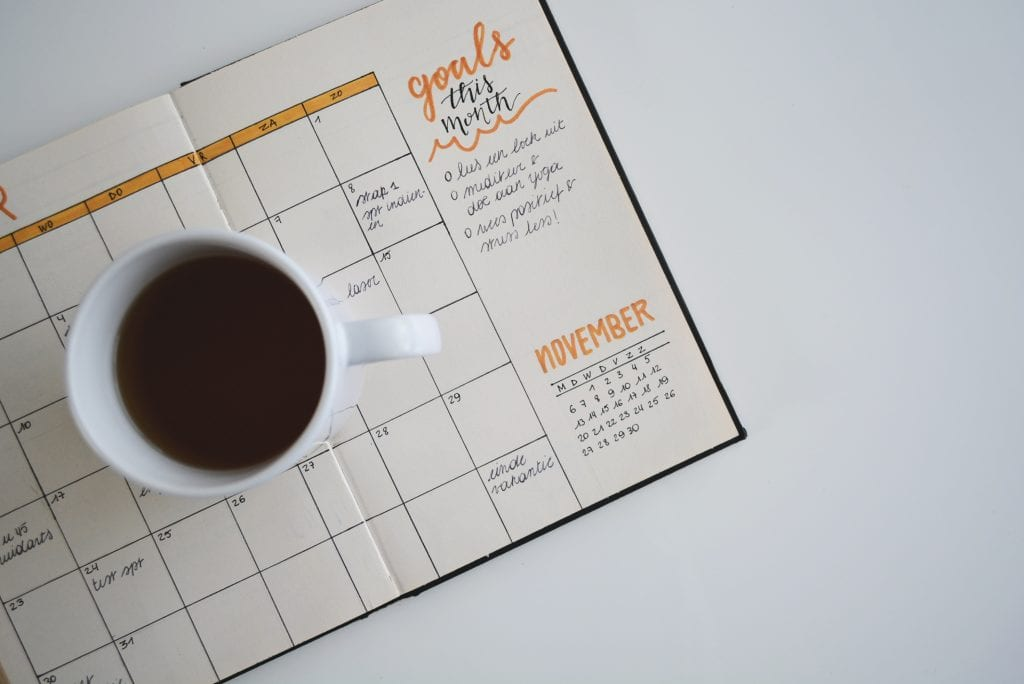 an open calendar with a cup of coffee placed on it is viewable from the top down.