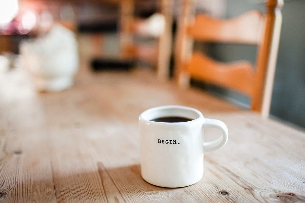"""a cup of coffee with the word """"begin."""" etched in it resting on a wooden table with wooden chairs in the background."""
