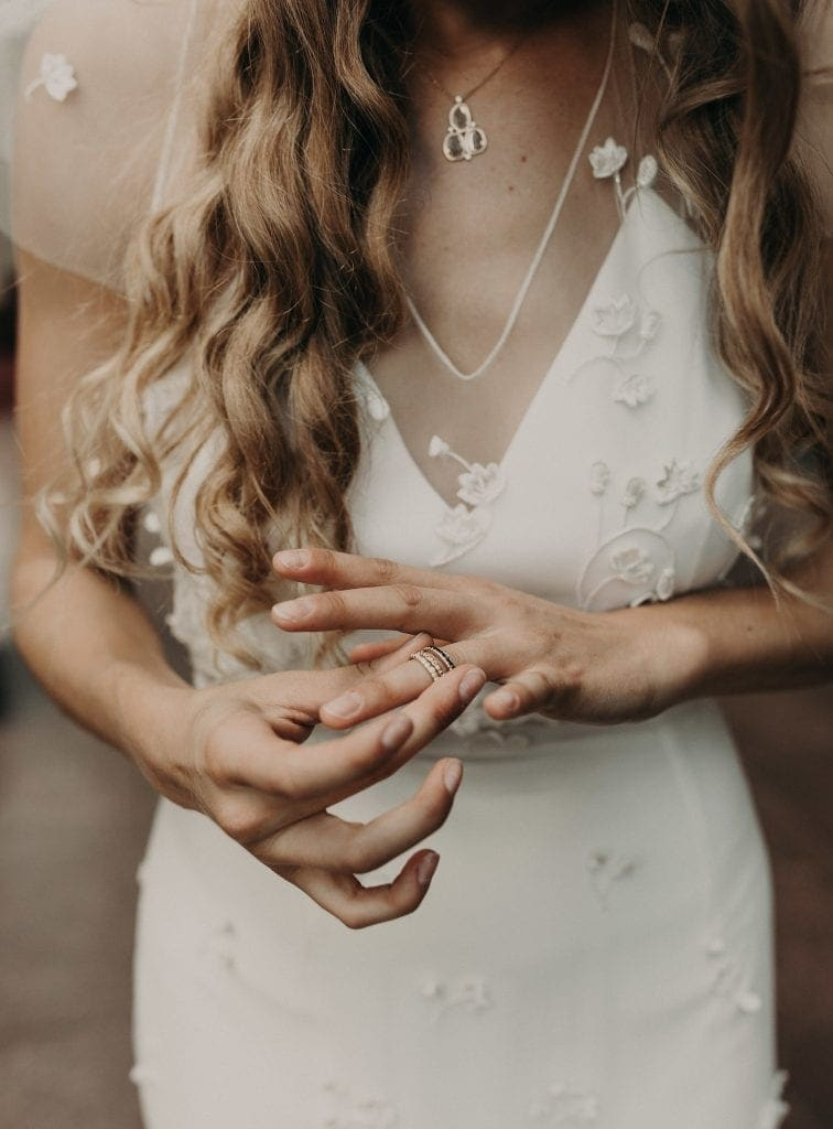 Close up shot on bride's hands as she places wedding ring on her finger. Photograph by Austin, Texas wedding photographer Nikk Nguyen.