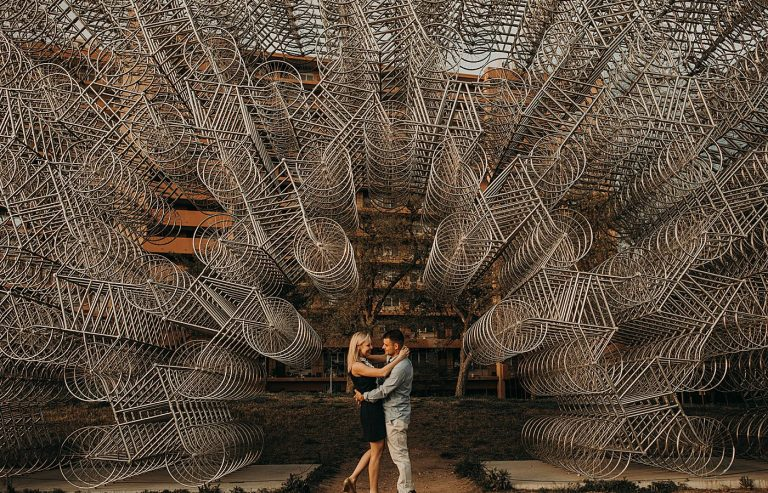 Bride to be and groom to be embrace during engagement session while standing centered in front of Ai Weiwei's Forever Bicycles in Austin, Texas. Photograph by Austin, Texas wedding photographer Nikk Nguyen.