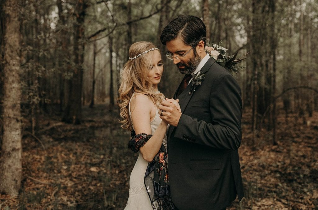 Bride and groom clasp hands facing each other in a forest at Dove Hollow Estate in Longview, Texas. Photograph by Austin, Texas wedding photographer Nikk Nguyen.