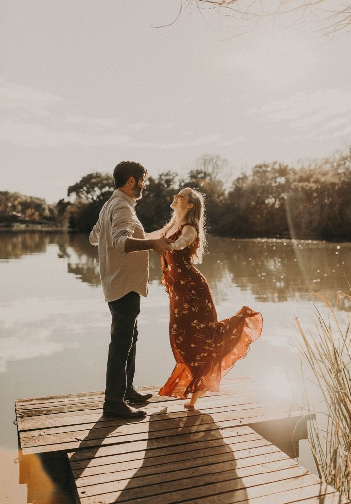 Engagement photo shoot with couple embracing while facing each other on a dock overlooking a lake. The bride to be in a red dress, kicks her left leg back as the she smiles at her partner. while at Laguna Gloria in Austin, Texas