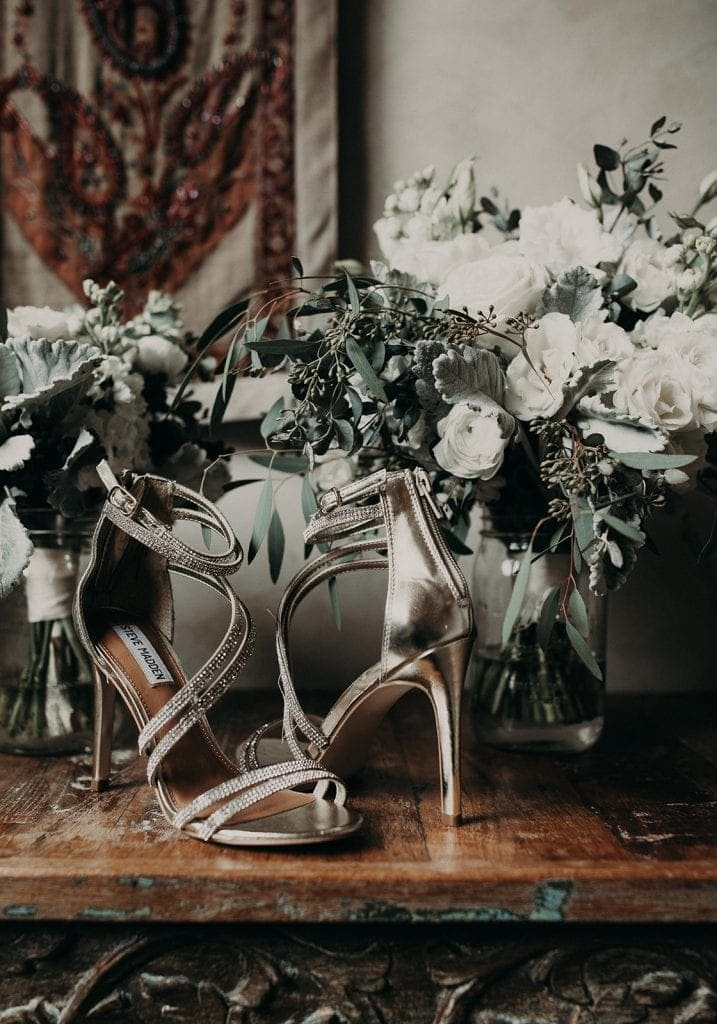 pair of wedding high heels on a wooden table in front of bridal bouquet and bridesmaid bouquet in glass jars in the background
