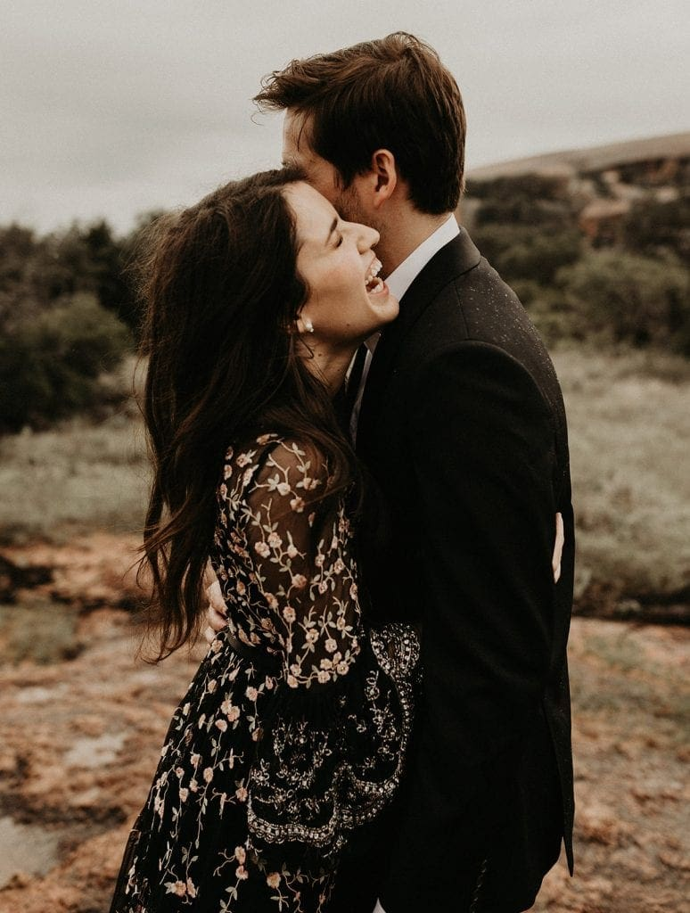 engagement photo shoot with couple embracing as the bride to be laughs over the groom to be's shoulder at Enchanted Rock in Fredericksburg, Texas
