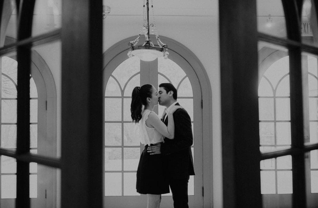 Black and white photo through a doorway of a couple kissing under a chandelier in the hallway of The Contemporary Austin, Laguna Gloria in Austin, Texas. Photograph by Austin, Texas wedding photographer Nikk Nguyen.