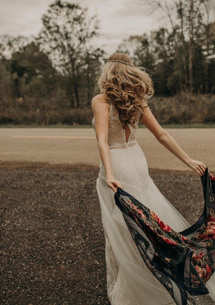 Bride in a white dress with her back towards the camera hold her arms out behind her with a shawl held in both hands. The wind blows the shawl and her hair back towards the camera.