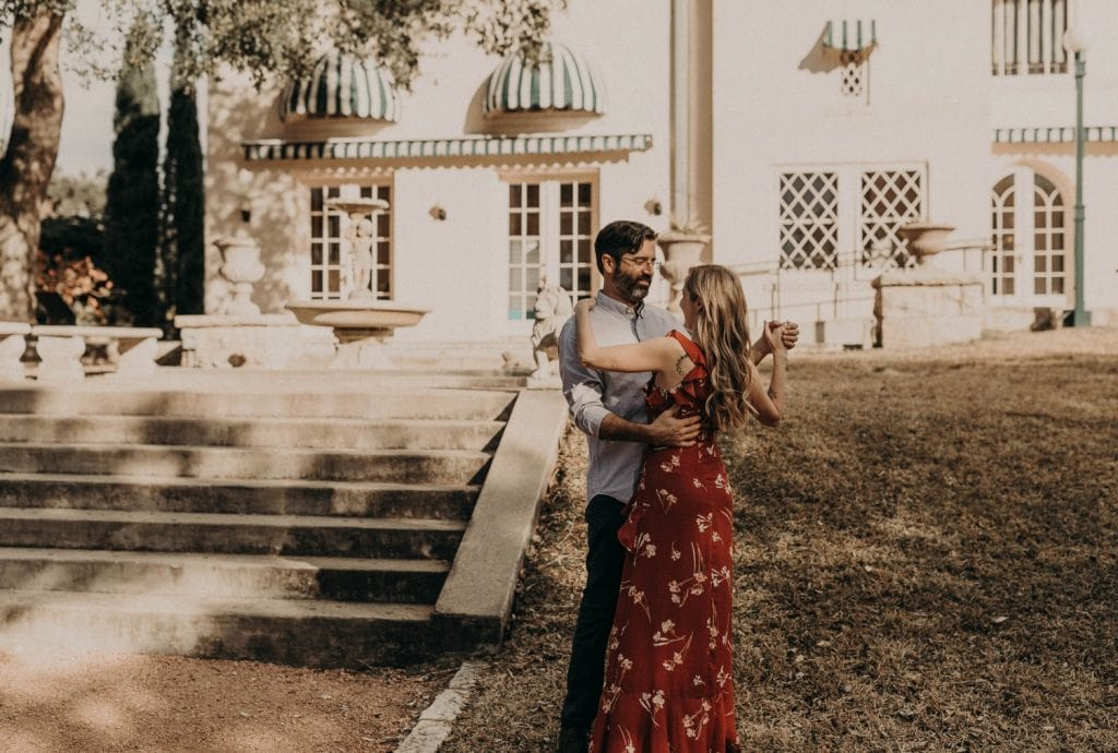 an engaged couple clasp hands and dance outside of Laguna Gloria in Austin Texas. Photograph by Austin, Texas wedding photographer Nikk Nguyen.