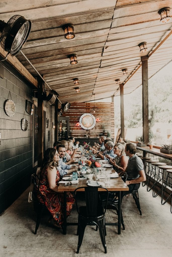 Group of people sitting at a table eating at a wedding in a rustic setting. Photograph by Austin, Texas wedding photographer Nikk Nguyen.