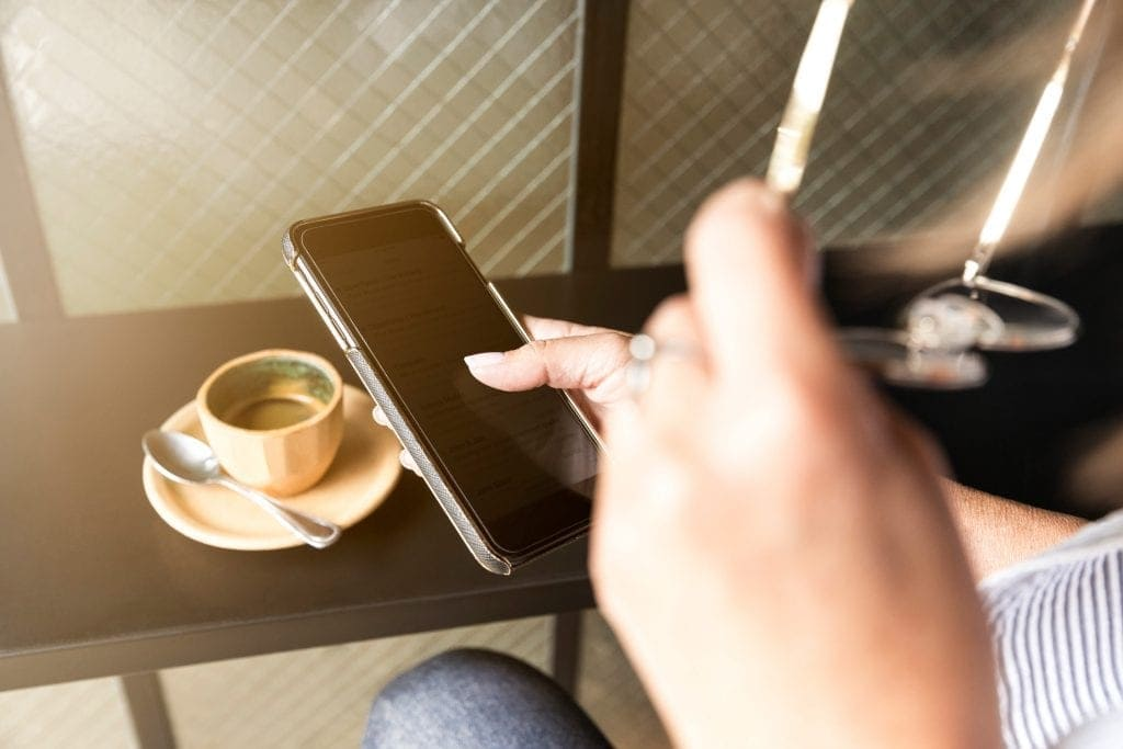 someone holds an iPhone with one hand and a pair of glasses in the other while looking at the iPhone screen. A cup of espresso on a plate with a spoon rests on a bar table in the background