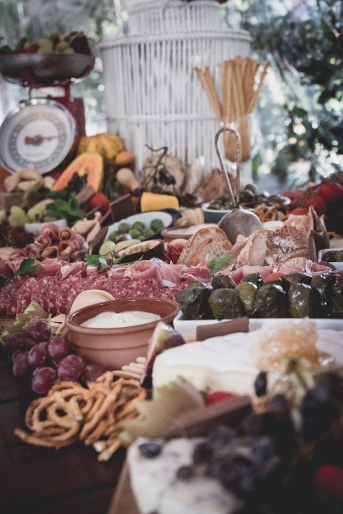 a wedding grazing table with grapes, meats, breads, cheeses, fruits and a scale