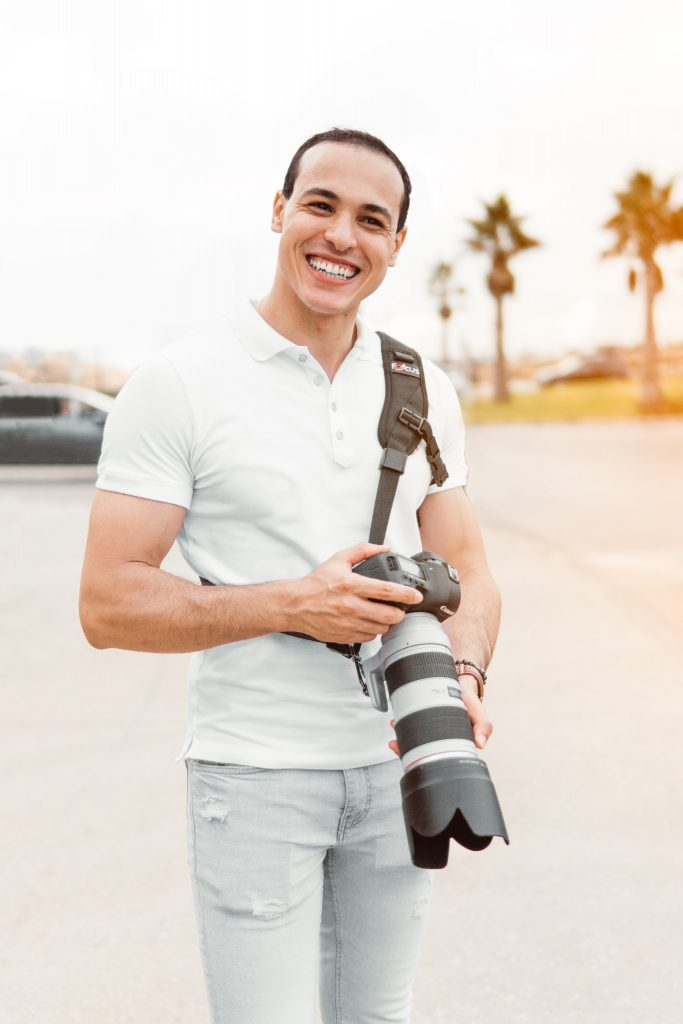a man in a white button up short sleeve shirt smiles while holding a camera. Palm trees are in the background.
