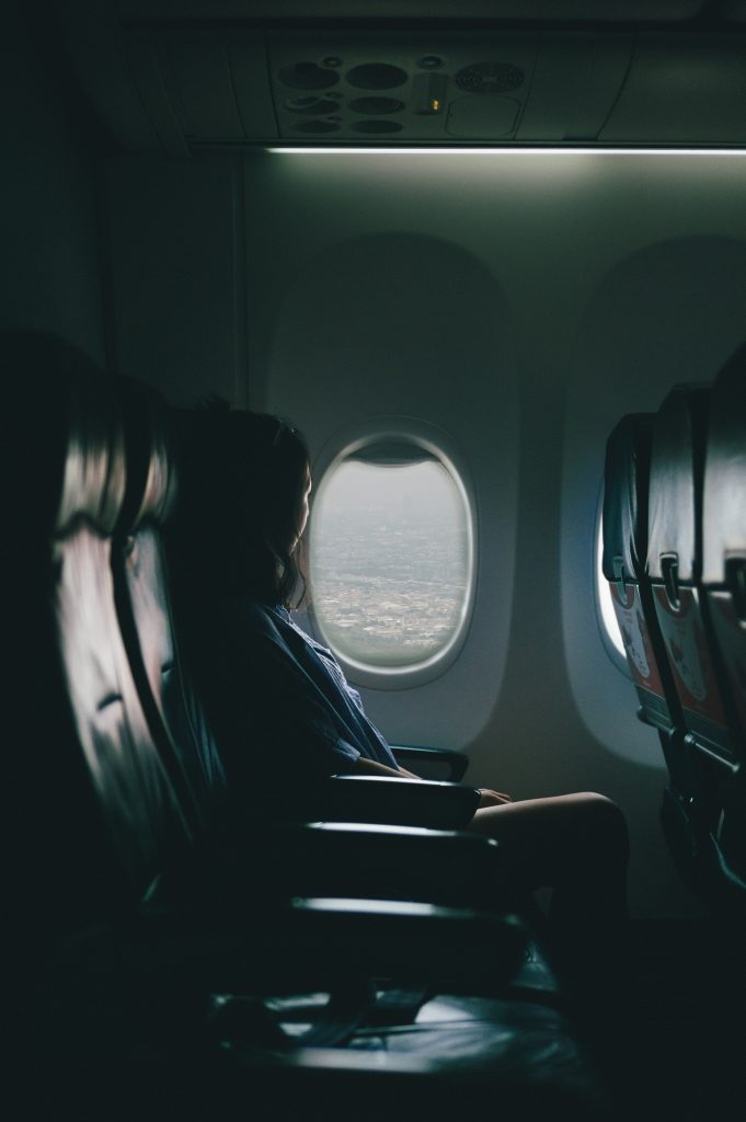 A young woman sitting in an airplane looking out the window