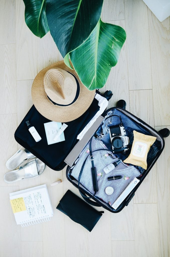 An open suitcase with clothes, a camera and a sunhat inside