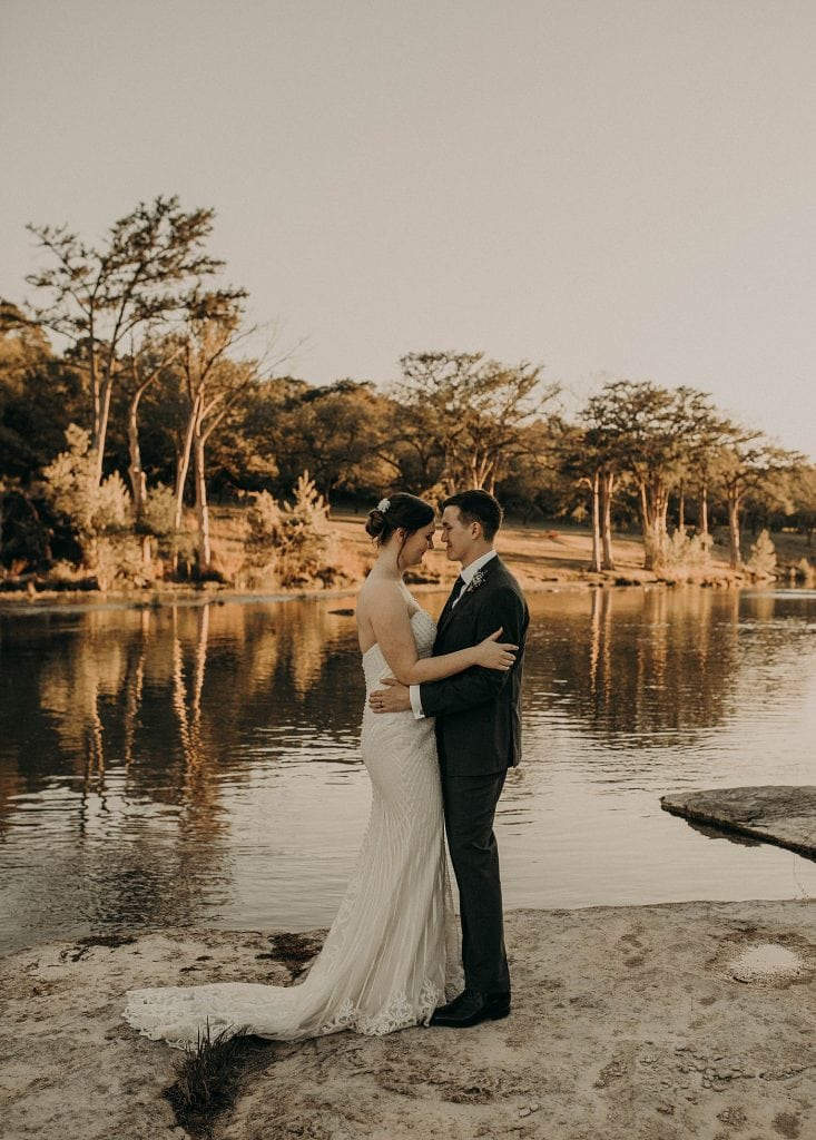 A bride and groom face each other embracing while standing in front of a pond and wooded area as the sun sets during a rustic wedding at The Waters Point Resort in Wimberley, Texas. Photograph by Austin, Texas wedding photographer Nikk Nguyen.