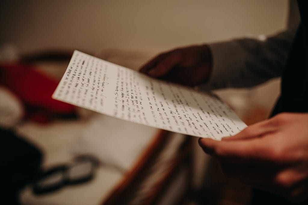 Close up of groom holding his hand written wedding vows. Photograph by Austin, Texas wedding photographer Nikk Nguyen.