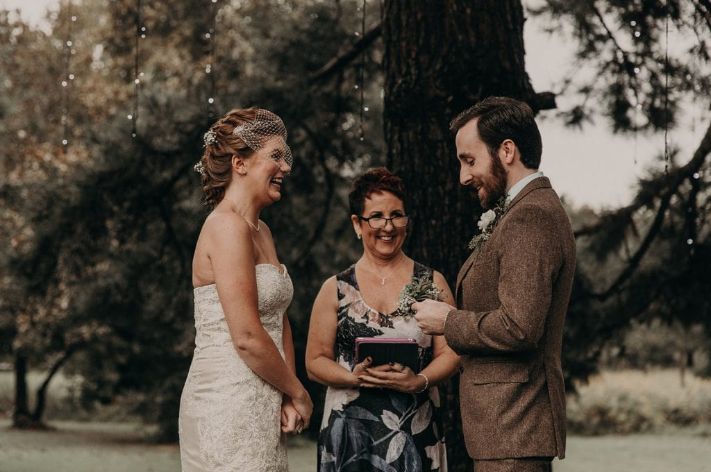 Groom reading his wedding vows to his bride as she smiles in a ceremony in Austin, Texas. Photograph by Austin, Texas wedding photographer Nikk Nguyen.