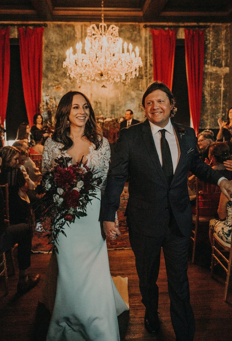 Bride and groom walk away from the altar hand in hand after being married at Palazzo Lavaca in Austin, Texas. They have big smiles on their faces. Photographed by Austin, Texas wedding photographer Nikk Nguyen.