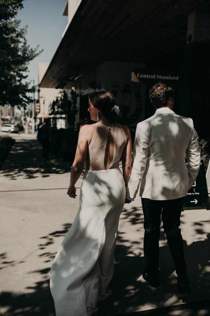 Bride and groom walking hand in hand on the sidewalk in downtown Austin during a congress hotel wedding. Photograph by Austin, Texas wedding photographer Nikk Nguyen.